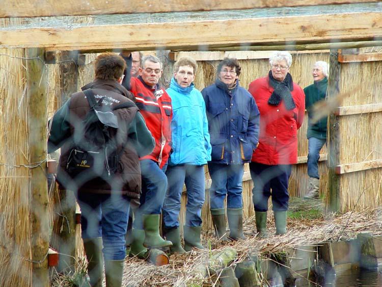 De bewoners krijgen uitleg over de eendenkooi in de vangpijp